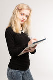 Blond Teen Girl Writing Notes On Notepad Stock Photo
