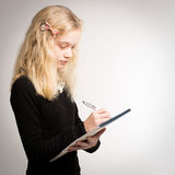 Blond Teen Girl Writing Notes On Notepad Royalty Free Stock Photo