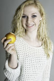 Blond teen holding an apple. Healthy young person holding an apple royalty free stock photography