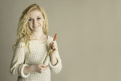 Blond teen holding pennywhistle. Blond teen holding a pennywhistle stock photography