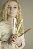 Blond teen holding recorders and a pennywhistle Royalty Free Stock Images