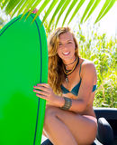 Blond teen surfer girl with green surfboard on car. Blond teen surfer happy girl with green surfboard on California convertible car Royalty Free Stock Image
