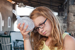 Blond teenage Caucasian girl puts ice to the head Royalty Free Stock Photography