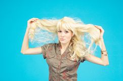 Blond Teenage Girl - 4. Pretty teenager feathering out her long, blond hair Stock Photography