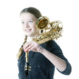Blond teenage girl holds saxophone in studio Stock Images
