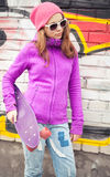 Blond teenage girl holds skateboard near by urban wall Royalty Free Stock Photos