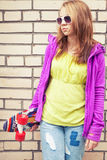 Blond teenage girl in jeans holds skateboard. Blond teenage girl in jeans, sunglasses and colorful sporty clothes holds skateboard near by urban brick wall stock photos