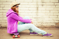 Blond teenage girl in jeans sits on her skateboard Royalty Free Stock Photos