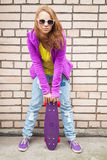 Blond teenage girl in jeans with skateboard. Blond teenage girl in jeans, sunglasses and sporty clothes holds skateboard near by gray urban brick wall stock images