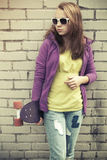 Blond teenage girl in jeans and sunglasses with skateboard Stock Photos