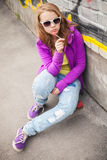Blond teenage girl with lollipop, vertical urban portrait Stock Images
