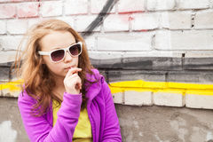 Blond teenage girl with lollipop, vertical urban portrait Royalty Free Stock Photos