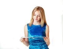 Blond teenage girl reading fashion magazine. Beautiful blond teenage girl reading fashion magazine on white background Royalty Free Stock Image