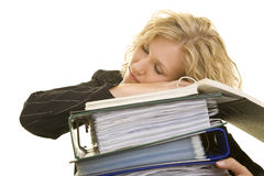Blond teenage girl sleeping. Blond teenage girl fallen asleep in the office with her head on top of a pile of files and folders due to overwork stock photos