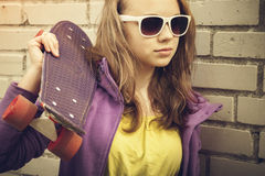 Blond teenage girl in sunglasses holds skateboard Royalty Free Stock Images