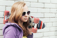 Blond teenage girl in sunglasses with a skateboard Stock Photos
