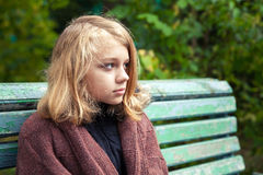 Blond teenage girl in woolen plaid sitting on bench Stock Photo