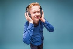 Teenager in headphones with a sour face listening to music Stock Photos