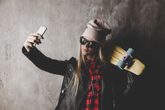Blond teenager girl in black sunglasses and pink hat with blue skateboard doing selfie in front of concrete wall. Royalty Free Stock Images