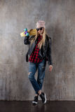Blond teenager girl in black sunglasses and pink hat with blue skateboard. In front of concrete wall. Stock Photo