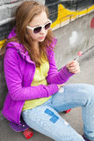 Blond teenager girl with a lollipop Royalty Free Stock Photos