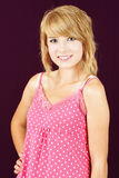 Blond teenager girl smiling. Portrait of cute and innocent yound blond teenager girl smiling, studio shot over deep pink or purple background Royalty Free Stock Image