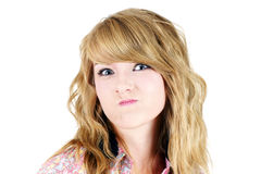 Blond teenager making unhappy funny face. Cute young blond teenager girl making a funny unhappy or upset face, studio shot on white Stock Image