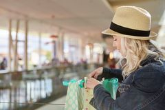 Blond teenager with straw hat in shopping mall. Looks in shopping bags Royalty Free Stock Photos