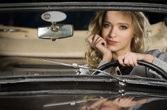 Blond temptation. Pretty young woman in an old car Royalty Free Stock Photography