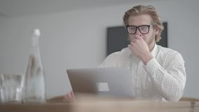 Portrait successful blond thoughtful man in glasses sitting at the table in a light comfortable office in front of. Blond thoughtful man in glasses sitting at stock video