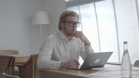 Blond thoughtful man in glasses sitting at the table in a light comfortable office in front of netbook. Handsome. Blond thoughtful man in glasses sitting at the stock footage