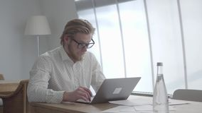 Confident blond thoughtful man in glasses sitting at the table in a light comfortable office in front of netbook. Blond thoughtful man in glasses sitting at the stock video