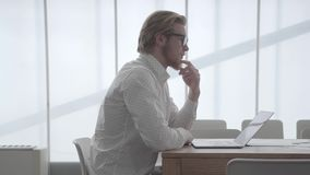 Blond thoughtful man in glasses sitting at the table in a light comfortable office in front of netbook and stroking his. Beard thinking about work. Handsome stock footage