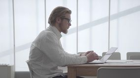 Blond thoughtful man in glasses sitting at the table in a light comfortable office in front of netbook and typing on. The keyboard. Handsome businessman writes stock video footage