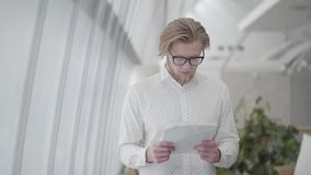 Blond thoughtful man in glasses standing in a light comfortable office reading papers. Handsome businessman involved in. Blond thoughtful man in glasses standing stock footage