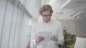 Portrait successful blond man in glasses standing in a light comfortable office reading papers. Handsome businessman. Blond thoughtful man in glasses standing in stock video