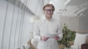 Portrait successful blond man in glasses standing in a light comfortable office holding paper looking at the camera. Blond thoughtful man in glasses standing in stock video footage