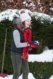 Blond tienermeisje die een sneeuwbal in sneeuw achtertuin maken stock afbeelding