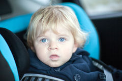 Blond toddler boy in safety car seat Royalty Free Stock Photography