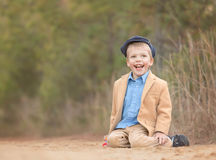 A blond toddler boy sitting on a sand and laughing Stock Photos