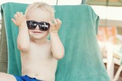 Blond toddler boy wearing sunglasses Stock Photo