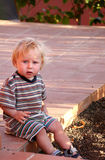 Blond toddler on sidewalk. A view of a little blond boy wearing a striped shirt and pants, outdoors and sitting on the edge of a brick sidewalk or patio royalty free stock photography