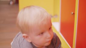 Blond toddler tries to open door of locker. Blond toddler trying to open door of locker stock video