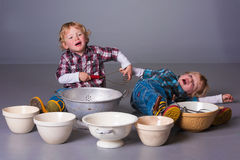 Blond toddlers playing with cooking utensils. Cute blonde twins fighting over cooking bowls and utensils royalty free stock image