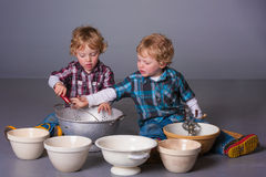 Blond toddlers playing with cooking utensils Stock Photos