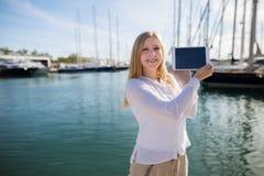 Blond tonåring med den utomhus- digitala minnestavlan Arkivbilder