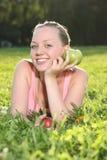 Blond tonåring som ligger i gräset Royaltyfri Fotografi