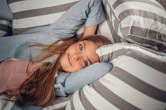 Blond tonårs- flicka som ligger på en soffa arkivfoton