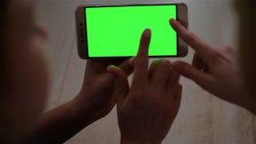 Blond tonårs- flicka som rymmer en smartphone med den gröna skärmen i landskapfunktionsläge i dagsljus stock video