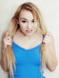 Blond tonårs- flicka som visar skadat torrt hår Royaltyfri Foto